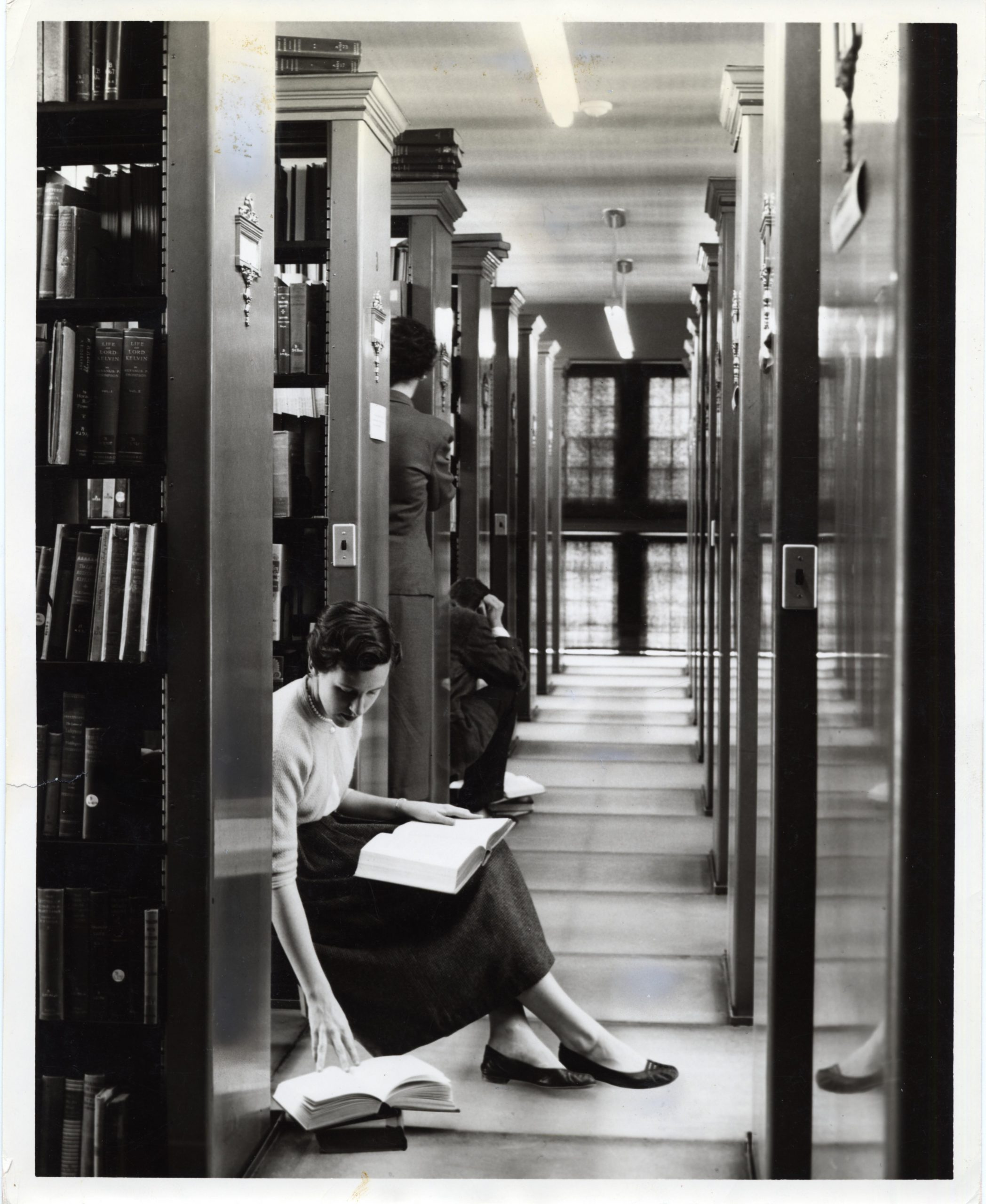 Photograph of students in between book stacks in Starr Library, in or around 1962