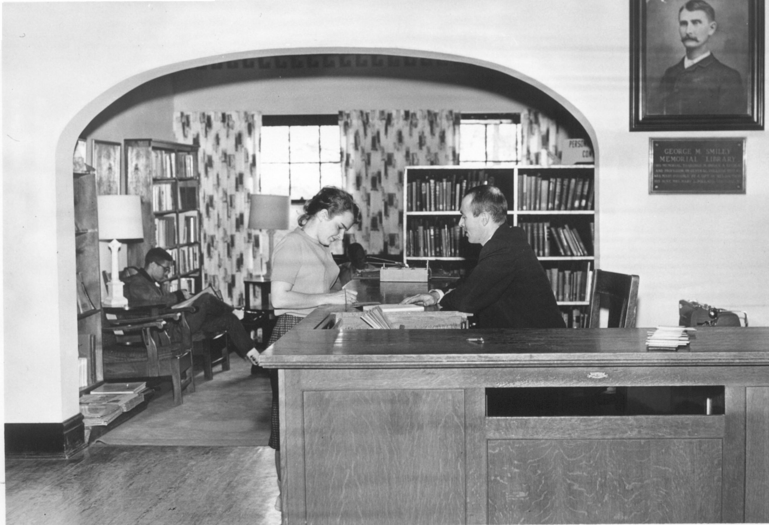 Black-and-white photograph of a male librarian assisting a female student at the circulation desk